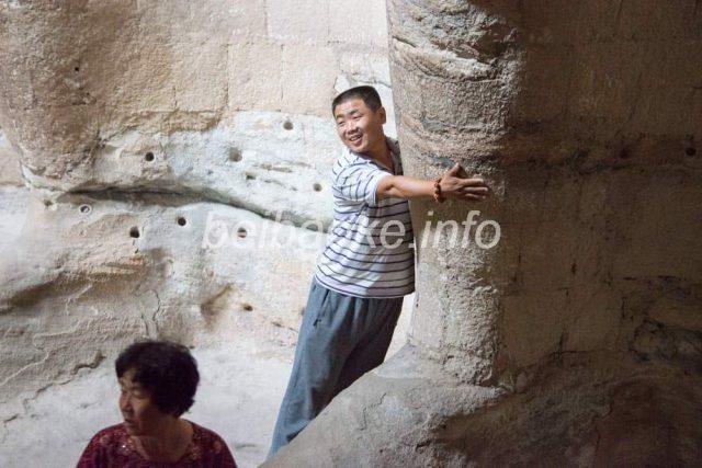 石仏に抱きつく中国人観光客